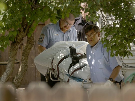 Tribune file photo:  Emergency Medical Technicians Ken Downs, right, and Tony Perez, from Great Falls Emergency Services remove a body from the scene of a murder-suicide Tuesday, July 1, 2003, in Great Falls. Two adults and two children were found dead with gunshot wounds Tuesday around 11:00 am.