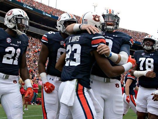 Auburn quarterback Jarrett Stidham (8) celebrates with Auburn wide receiver Ryan Davis (23) during the NCAA football game between Auburn and Ole Miss on Saturday, Oct. 7, 2017, in Auburn, Ala.