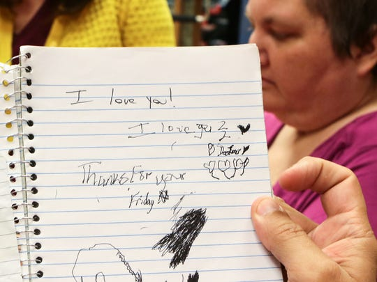 The Rev. Gregg Loner holds a notebook bearing the words 'I Love You, I love you 2 Dee Loner,' showing a recent note the couple wrote each other. Near him, his wife Dee works on occupational therapy with Amanda Barrieau at Roger C. Peace Rehabilitation Hospital in Greenville.
