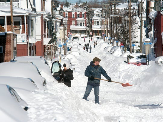Chris, right, and Milly Beck clean snow from their