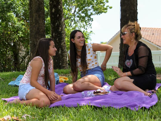 Transgender teen Jazz Jennings, left,  appears with Ari at the park with their mother Jeanette.