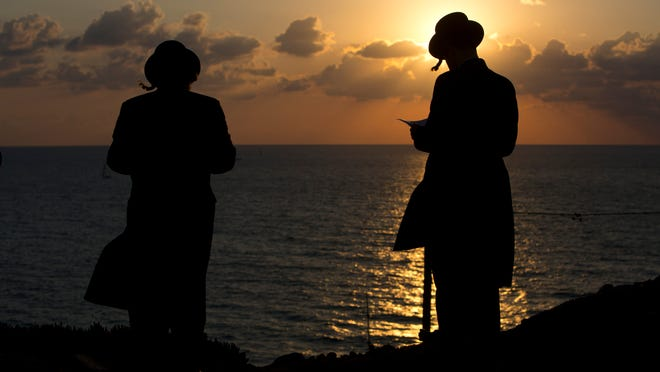 "Ultra-Orthodox Jews of the Hassidic sect Vizhnitz gather on a hill overlooking the Mediterranean sea as they participate Thursday in a Tashlich ceremony in Herzeliya, Israel. Tashlich is the practice of going to a large flowing body of water and symbolically ""throwing away"" their sins."
