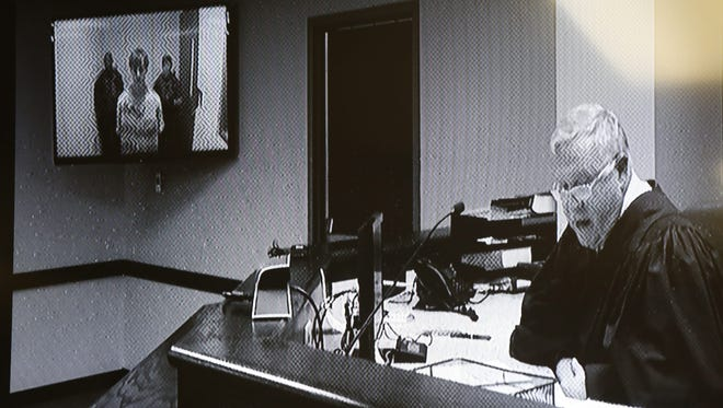 A photograph of a courthouse monitor displaying the bond hearing for suspect Dylann Roof.