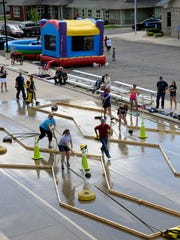Albany firefighters had people use a hose to spray a bowling ball down the obstacle course on Saturday, Aug. 6, in downtown Albany.