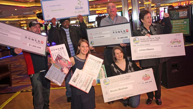 From left back row, Luis Ospina of Sleepy Hollow, Nathaniel Brown of Elizaville, John Dubbioso of Thornwood, Julieta Ribeiro of Scarsdale, and Nicola Meehan of Pearl River were announced as five Lottery millionaires from The New York Lottery's Gretchen Dizer, front row at Empire City Casino at Yonkers Raceway on March 14, 2014.