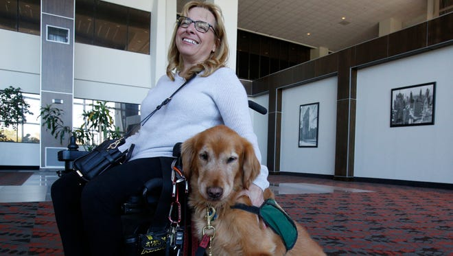 Elena Berger of New Rochelle with her service dog Garrison, a Golden Retriever in Harrison on Oct. 14, 2016.  Berger, who is wheelchair bound, has a neurological disorder making her physically too weak to do mundane tasks such as opening door, pushing an elevator button or picking up something that may have fallen on the floor.