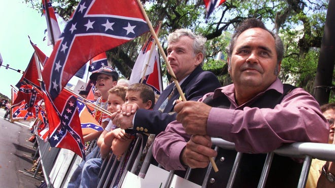 Supporters of the Sons of Confederate Veterans hold Confederate flags during the 2003 Springtime Tallahassee parade, in which the SCV was not allowed to participate. IN later years, the Sons of Confederate Veterans did appear in the Springtime parade.