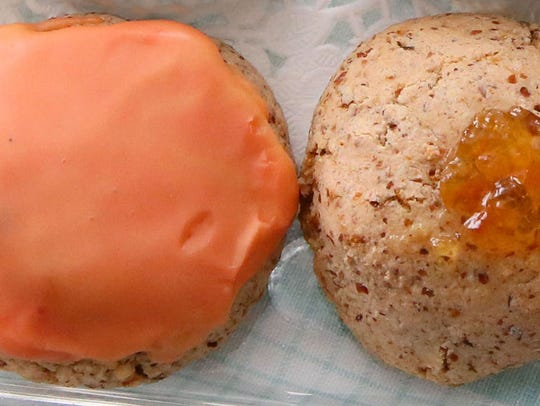 Orange macaroons can be frosted, topped with a dab