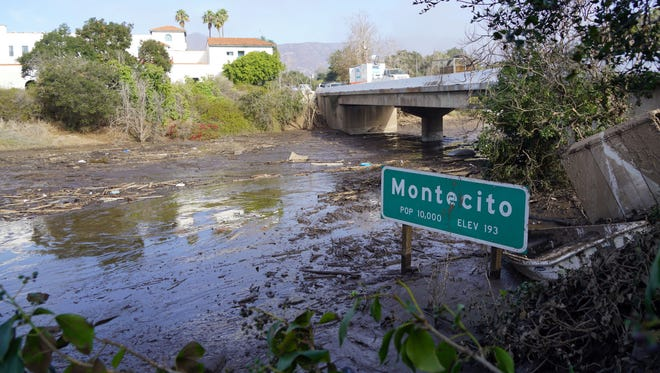 A sign on U.S. Highway 101 sits partially buried in mud from the mudslides in Montecito, Calif.