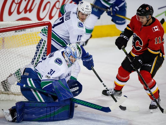 Vancouver Canucks goalie Anders Nilsson, left, from Sweden, traps a shot from Calgary Flames' Mikael Backlund, also from Sweden, during first-period NHL hockey game action in Calgary, Saturday, Dec. 9, 2017. (Jeff McIntosh/The Canadian Press via AP)