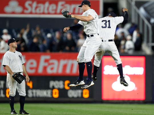 New York Yankees left fielder Brett Gardner (11) watches as right fielder Aaron Judge, center, and center fielder Aaron Hicks celebrate the Yankees' 9-6 victory over the Boston Red Sox in a baseball game in New York, Wednesday, May 9, 2018. (AP Photo/Kathy Willens)