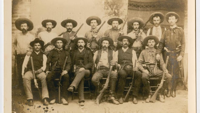 Photograph of a group of Texas rangers. Each ranger is holding a rifle of their own. Identified on the back are Jim King, Bass Outlaw, Riley Boston, Charles Fusselman, -- Derbin, Ernest Rodgers, Charles Barton, Walter Jones, Bob Bell, Cal Aten, Captain Frank Jones, Walter Durbin, JIm Robinson, and Frank Schmidt.