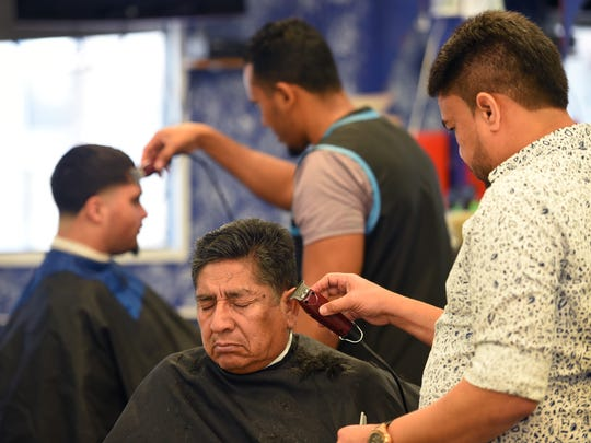 Barber Carlos Martes trims the hair of his customer Cesar Yanez of Clifton at Aquilino's Barber Shop in Passaic in March.