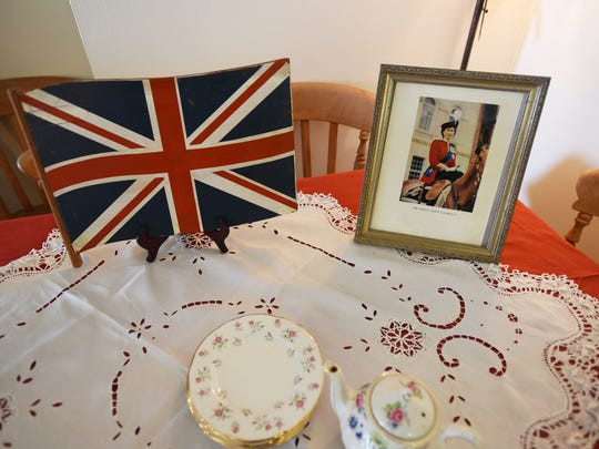 Photo of Queen Elizabeth and the Union Jack displayed on a table as members of the Daughters of the British Empire, an organization for women of British birth or lineage, 