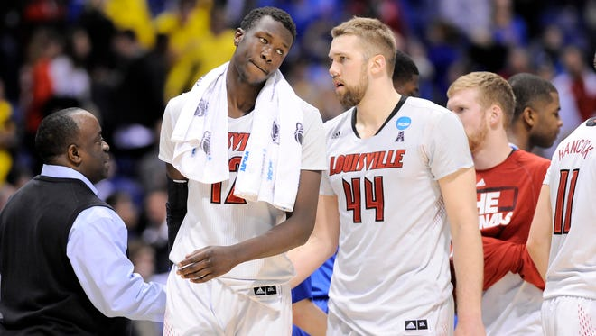 Louisville forward/center Mangok Mathiang (12) and forward Stephan Van Treese (44) leave the court after losing to the Kentucky Wildcats Friday in the NCAA Midwest Region semifinals at Lucas Oil Stadium.