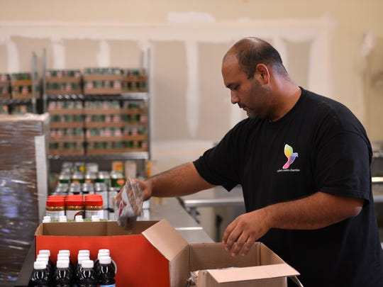 Alejandro Castro prepares items for people who come to the Ruben Castro Charities food pantry at Moorpark College on Tuesday evening.