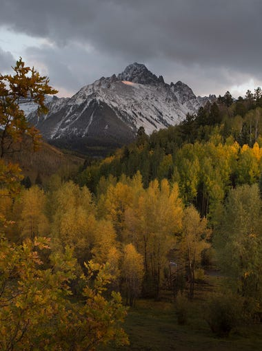 Fresh snow covers Mt. Sneffels, rising 14,157 feet in elevation, above a patch of fall colors near Ridgway, Colorado on Saturday, September 22, 2017.
