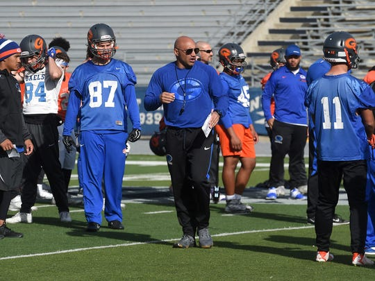 Bishop Gorman head football coach Kenny Sanchez, middle, runs practice Friday in preparation for the state championship game against Reed at Mackay Stadium in Reno.
