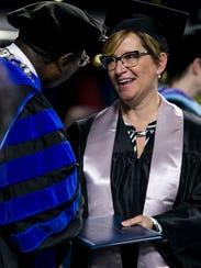 Trishia Warrick smiles as she receives her diploma