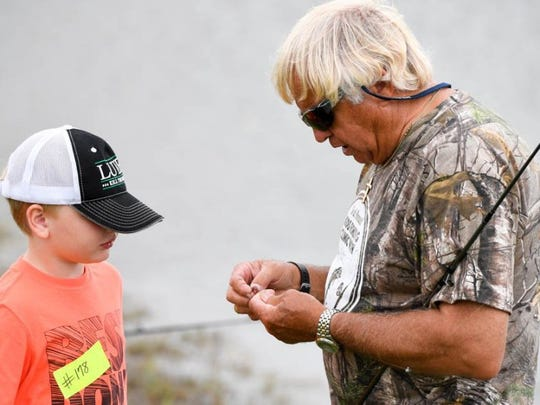 Professional angler and TV host Jimmy Houston gives Luke Gerhardt some professional advice on putting a worm on a hook during a past  Kids Fishing Clinic held at Expressway Chevrolet in Mount Vernon.