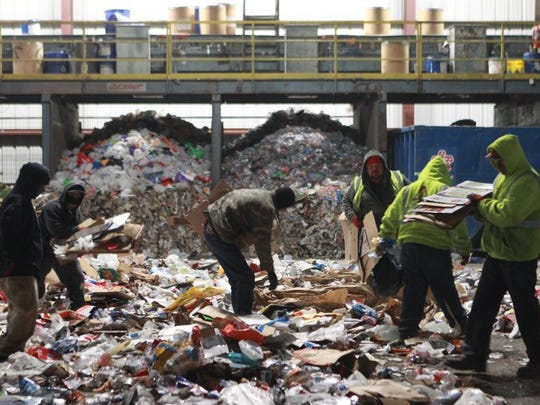Employees at Butts Recycling Inc. separate cardboard from other recyclables.