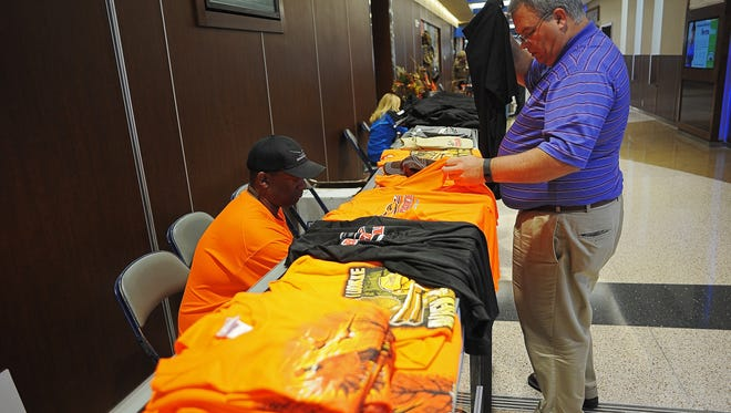 Arthur Radcliffe, of Greenwood, S.C., checks out some Roosterwear at Roosterwear president/CEO Kenny Fields' booth Thursday, Oct. 15, 2015, at the Sioux Falls Regional Airport in Sioux Falls. Hunters from all over the country filed through the Sioux Falls Regional Airport Thursday ahead of the pheasant season opener Saturday.