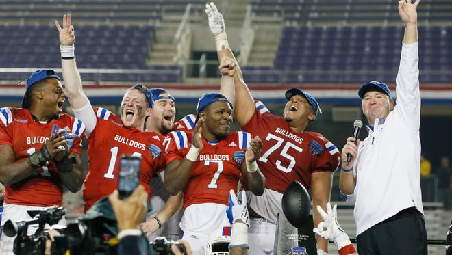 Louisiana Tech Bulldogs head coach Skip Holtz (right) celebrates winning the game with offensive lineman Darrell Brown (75) and safety Xavier Woods (7) and quarterback Ryan Higgins (14) and safety Lloyd Grogan (11) after the game against the Navy Midshipmen at Amon G. Carter Stadium. Louisiana Tech won 48-45. Mandatory Credit: Tim Heitman-USA TODAY Sports
