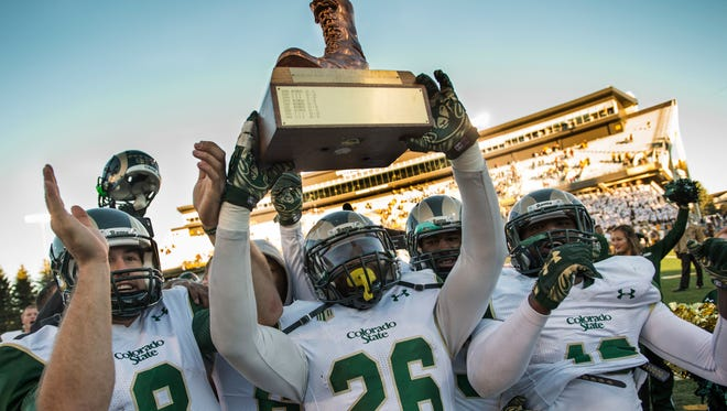 Kevin Pierre-Louis hold the Bronze Boot as he and his CSU teammates celebrate with the traveling trophy after winning last year's Border War game over Wyoming in Laramie. The rivals will meet for the 108th time Saturday night at Hughes Stadium.