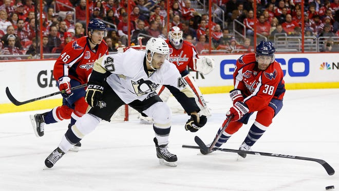 Washington Capitals defenseman Jack Hillen (38) slashes Pittsburgh Penguins center Maxim Lapierre (40) while battling for the puck in the second period at Verizon Center.