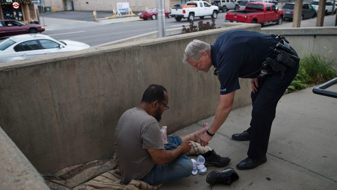 Loveland Police Sgt. Bob Shaffer, right, checks on a homeless man, looking over his feet that are damaged due to walking in waterlogged shoes, Friday, July 21, 2017, in downtown Loveland. Shaffer suggested the man stay off his feet until they and his shoes were dry to keep from further damaging his feet.