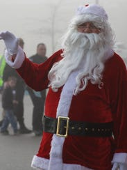 Santa waves to the children participating in the Shop
