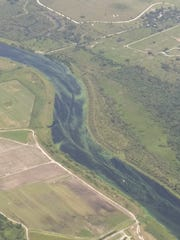 An aerial image of the Caloosahatchee River shows blue-green algae on the surface