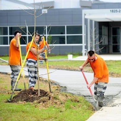 Lafayette Parish inmates work on a concrete walkway