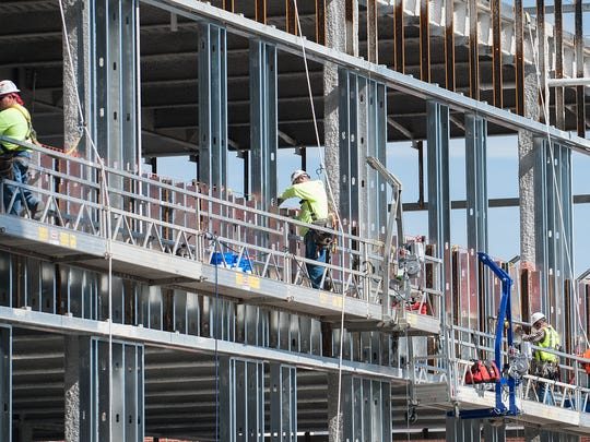 Construction workers tend to the side of the high-rise building being established at OhioHealth MedCentral Health System. The new facility will include 12 surgery suites and join some of the health system's specialty lines of service under one roof.