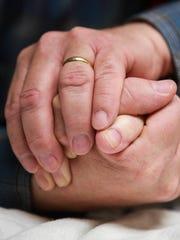Baptist Health chaplain Jim Ivey holds hands with patient