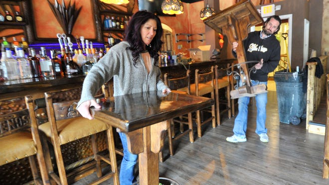 Self-employed Christy Sann, left, and Steve Arnold, bring in tables Thursday afternoon they furnished for Jalapenos Mexican Restaurante & Bar in downtown Wausau.