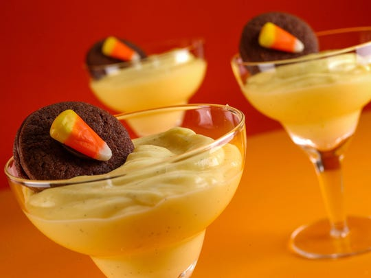 Vanilla pudding is piled in decorative glasses then garnished with chocolate-filled sandwich cookies, festively accessorized.