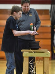 Eighth-grade student Kyle Selner and math teacher Tyler Thrune cringe as Selner's tower begins to crumble and scatter before he was able to add another weight during the Tower Challenge at Luxemburg-Casco Middle School. The weight plates represented 58 pounds supported on two ounces of balsam.