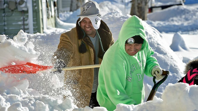 Jose Sanchez, left, and Irwin Perez are in good spirits as they shovel snow Sunday,  Jan. 24, 2016 along Garfield Street, Chambersburg. Winter storm Jonas dropped a few feet of snow in the area.