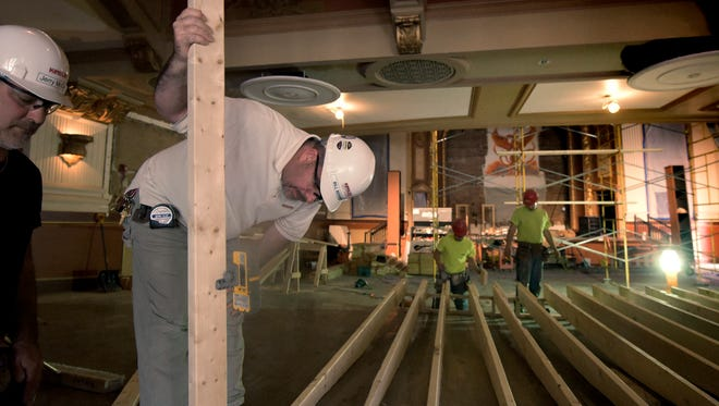 In this file photo, Kinsley Construction superintendant Bill Bergman and employee Jerry McCue, left, use laser measuring to level the floor of the new concession area they were building at the Capitol Theatre Monday, May 14, 2018. The greatest gains in Pennsylvania's May employment report were in construction and trade, transportation and utilities. Bill Kalina photo
