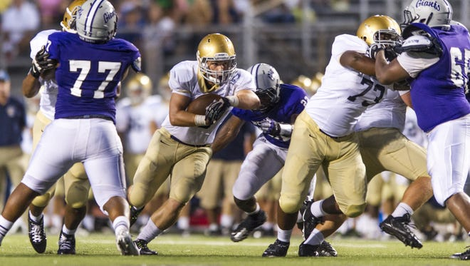 Cathedral High School junior Evan Christopher (40)  rushes the ball through the Ben Davis defense during the second half of action at Ben Davis High School, Friday, August 22, 2014. Ben Davis High School hosted Cathedral High School in varsity football action. Ben Davis won the season opener over Cathedral 44-19.