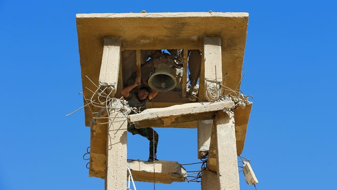 In this Nov. 13, 2016, file photo, an Iraqi Christian soldier from the Nineveh Plain Protection Unit fixes the bell of the St. Addai church, which was damaged by Islamic State fighters during their occupation of Keramlis village.