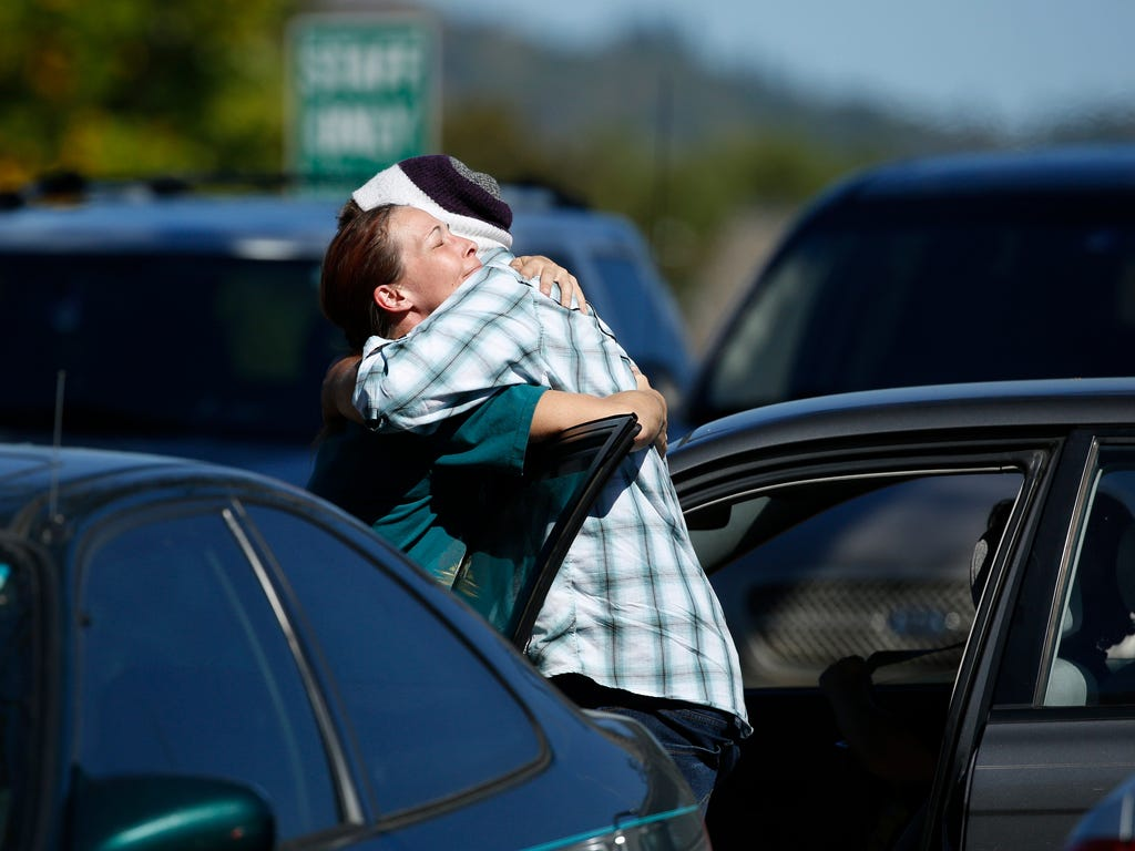 Student Mathew Downing, right, is hugged by a woman as they return to Umpqua Community College in Roseburg, Ore.