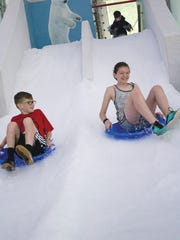 """Children tube down a 120-foot-long slope at the Philadelphia Zoo's """"Winter"""" exhibit."""