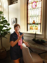 Pam Stevenson pauses in her Bell Tower condo on Milford's East Commerce Road on Sept. 5. Stevenson and her husband moved into the converted church condo in July of 2016. Their condominum has church fixtures like this lower level's stained glass window.