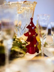 The centerpiece vase can be filled with red ribbons or roses while red glass tree ornaments can replace Thanksgiving elements.