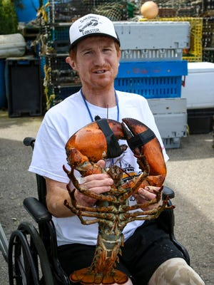 Sakonnet Lobster, Doug Mataronas of Sakonnet Lobster shows off one of the bigger lobsters at the store.