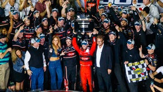 Austin Dillon, center, celebrates with the trophy in victory lane after winning the 60th annual Daytona 500.
