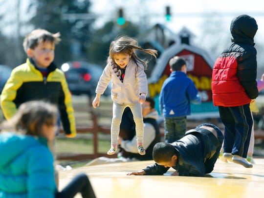 Anna Rice, 3, of Pittsford is airborne next to David Rivera, 6, of Rochester as he falls while playing on the Jumping Pillow.