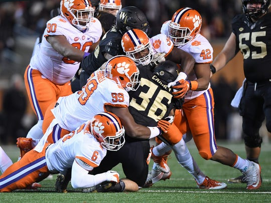 Clemson linebacker Dorian O'Daniel (6), defensive lineman Clelin Ferrell (99), linebacker Kendall Joseph (34), and defensive lineman Christian Wilkins (42) bring down Wake Forest tailback Cade Carney (36) during the 1st quarter at Wake Forest's BB&T field on Saturday, November 19, 2016.